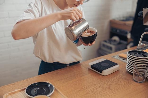 Молодая женщина делает капучино в кафе