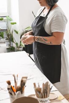 陶器工房で土鍋を作る若い女性