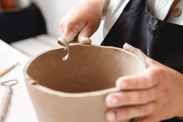 Young woman making earthen pot in pottery workshop