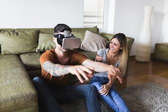 若い女性は彼女のボーイフレンドの楽しさを家庭でバーチャルリアリティの眼鏡で