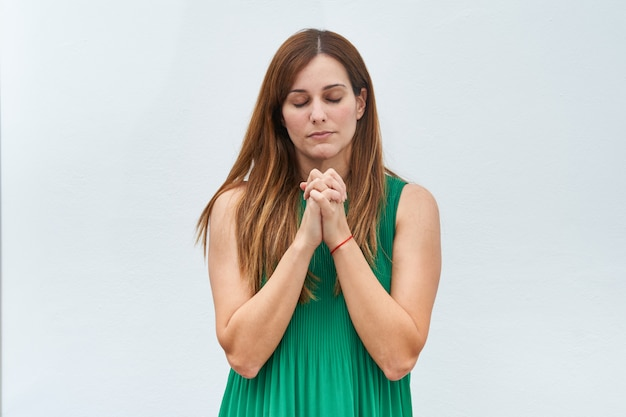 Young woman making the gesture of praying on a white background.