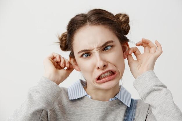 口をねじれたエッチないたずら者である間抜けな顔を作る若い女性。目を凝らして浮かんでいるカジュアルな服装の女性の顔をゆがめる女優。閉じる