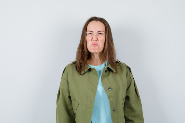 Young woman making grimace in green jacket and looking grumpy , front view.