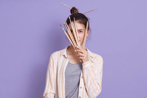 Young woman making hairstyle with painting brushes, holding brushes in hands and covering her face with it