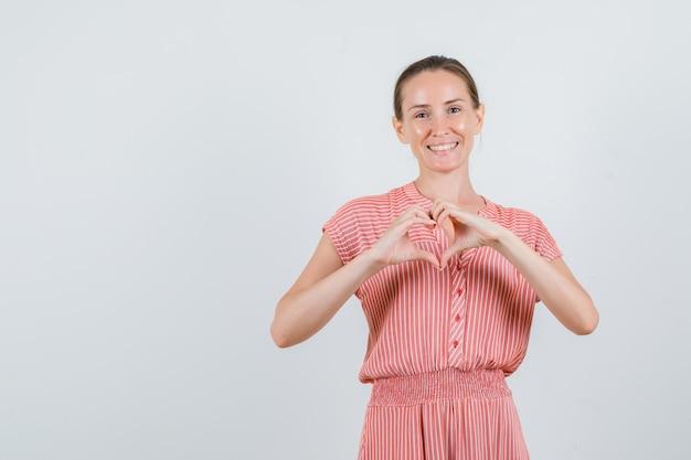 Молодая женщина делает форму сердца руками в полосатом платье и выглядит весело. передний план.