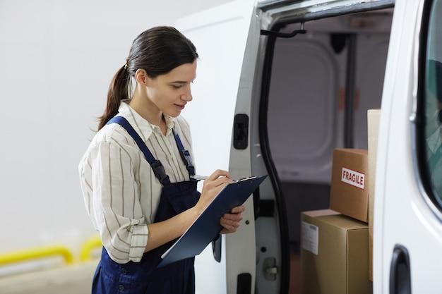 Молодая женщина делает заметки в буфере обмена и регистрирует коробки в грузовике перед доставкой