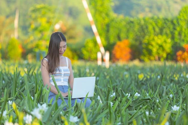 花畑に座ってメモ帳でメモをとる若い女性