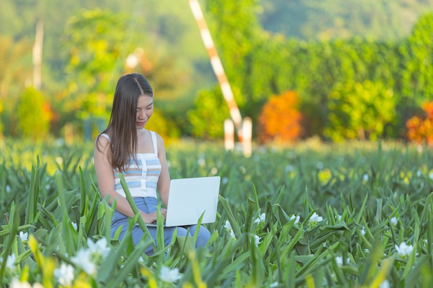 Young woman making notes in notepad while sitting in the flower garden