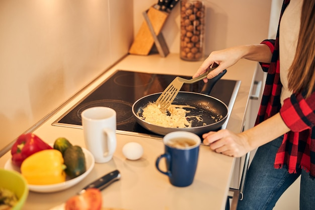 Young woman making an omelet in the frying pan