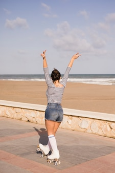 Young woman making peace sign gesture walking on the side walk near the beach