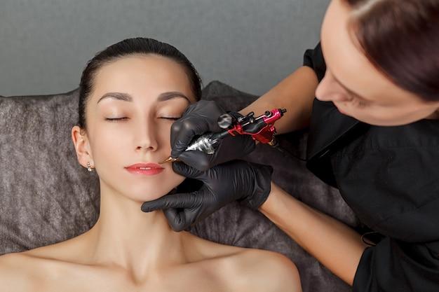 Молодая женщина делает перманентный макияж в косметологическом салоне