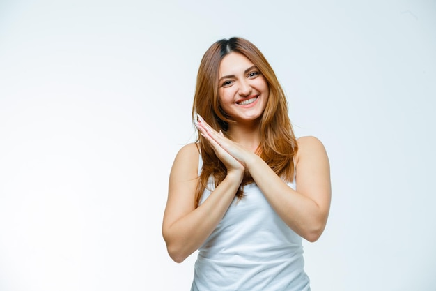 Young woman making pillow gesture while smiling