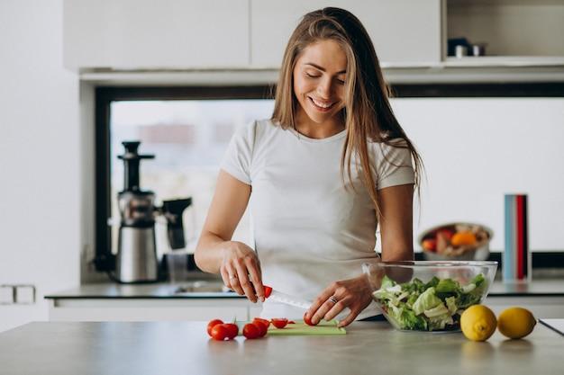Молодая женщина делает салат на кухне