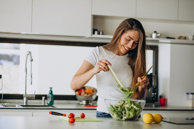 Young woman making salad at the kitchen