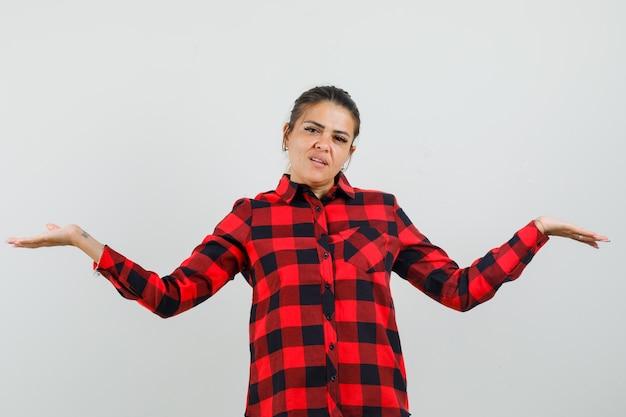 Молодая женщина делает жест весов в проверенной рубашке и выглядит уверенно. передний план.