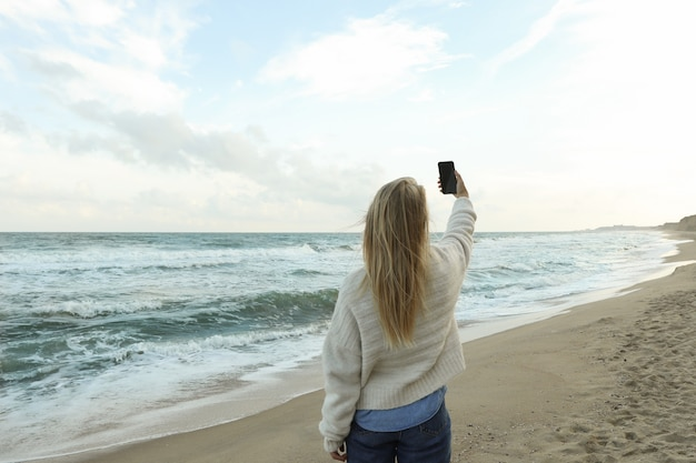 砂浜のビーチで自分撮りを作る若い女性