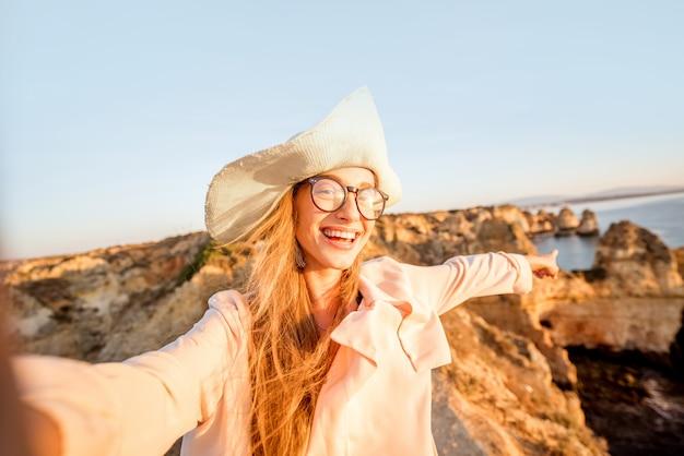 ポルトガル南部のラゴスを旅する日の出の間に岩の多い海岸線で自分撮りの肖像画を作る若い女性