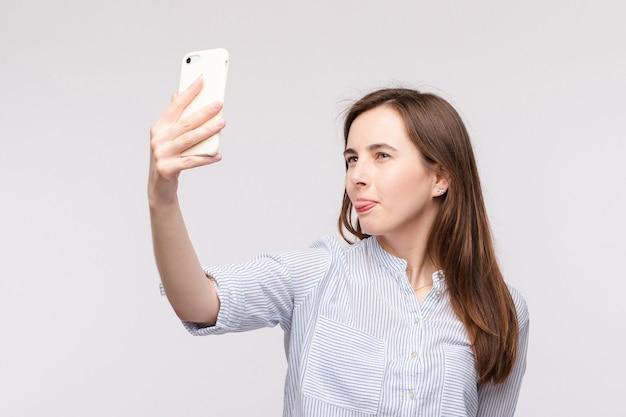 Молодая женщина делая selfie с smartphone.funny лицом и вставляя язык на камеру пока делающ selfie на сотовом телефоне