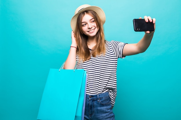 Young woman making a selfie on your smartphone sitting with colored bags for shopping
