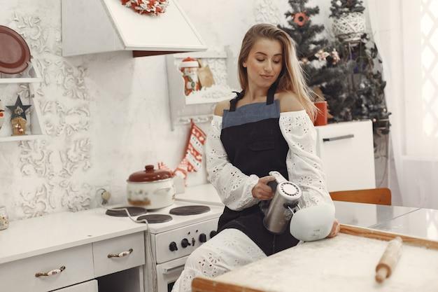 Giovane donna che produce biscotti a forma di per natale. soggiorno decorato con decorazioni natalizie sullo sfondo. donna in grembiule.