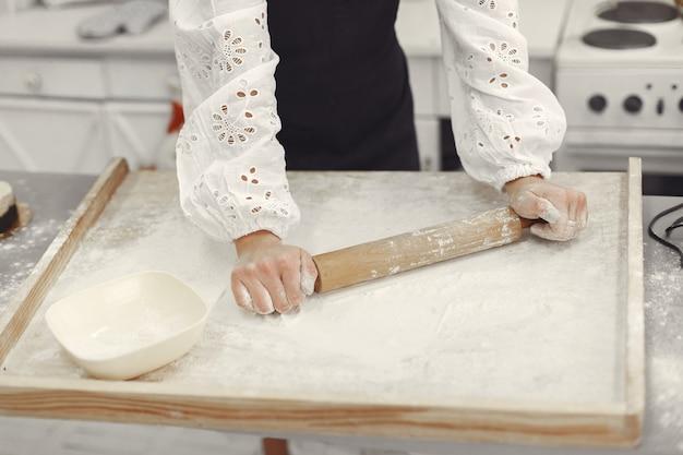 Giovane donna che produce biscotti a forma di