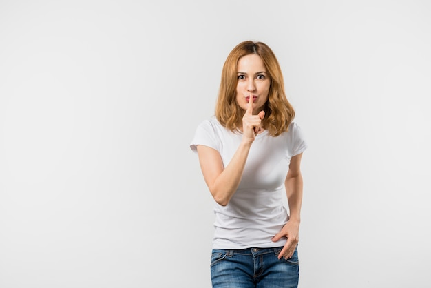 Young woman making silence gesture with finger on lips against white background