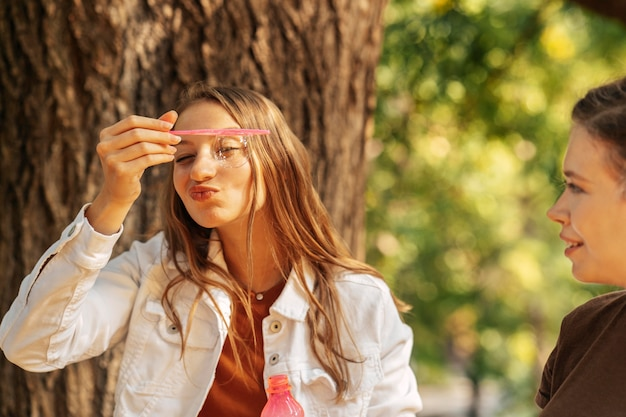 彼女の友人の隣にシャボン玉を作る若い女性