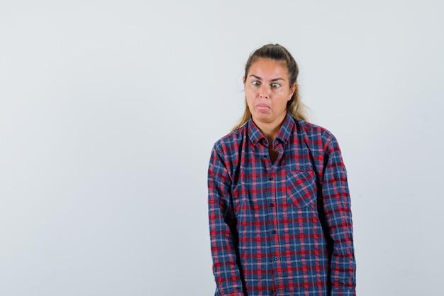 Молодая женщина делает косоглазие для удовольствия в клетчатой рубашке и выглядит удивленным. передний план.