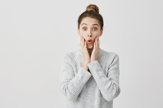 Young woman making surprise with facial expressions and touching her cheeks. girl in fashion being excited to know interesting gossip goggle at talker. human emotions