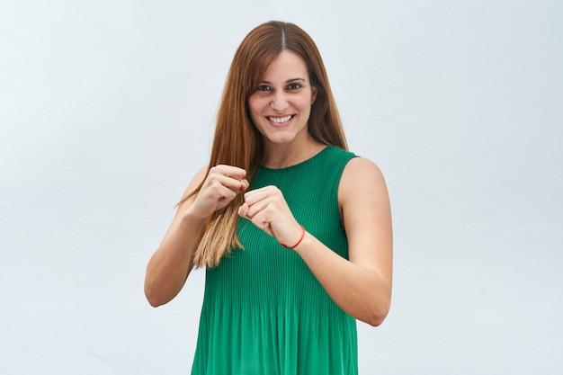 Молодая женщина делая жест быть готовым на белой предпосылке.