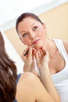 Young woman making-up her friend using lipstick and eye shadow