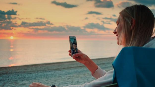 ビーチでスマートフォンを使って友達にビデオ通話をする若い女性