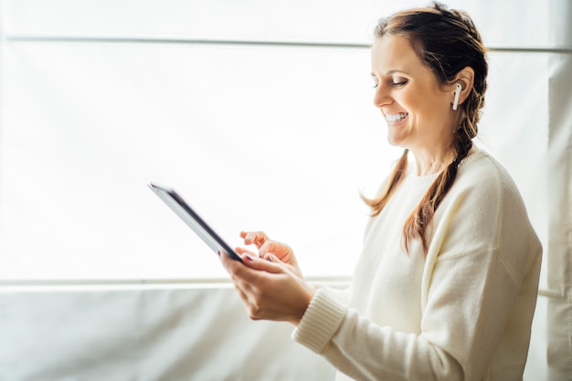 Young woman making a video call with a tablet and headset
