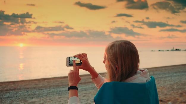 海岸に座ってスマートフォンで日没のビデオを作る若い女性。背面図