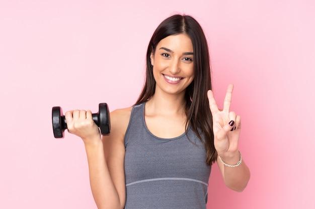 Молодая женщина делает тяжелой атлетике, изолированных на розовой стене, улыбаясь и показывая знак победы