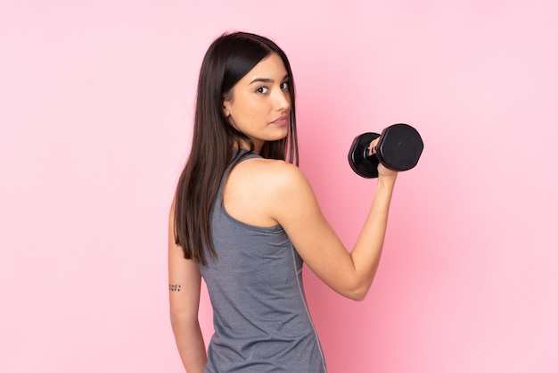 Young woman making weightlifting isolated on pink wall