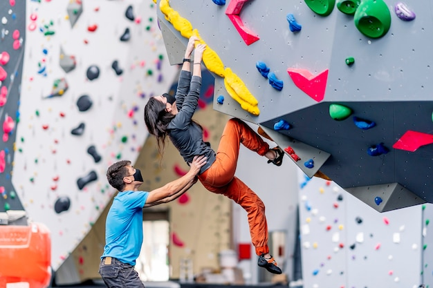 A young woman and a man climbing climbing wall practicing rock climbing.