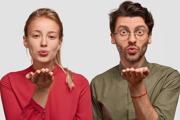Young woman and man fold lips, hold palms near mouthes, blow air kiss, have romantic look, love expression, wear fashionable clothes, isolated over white wall. sweet kiss by air