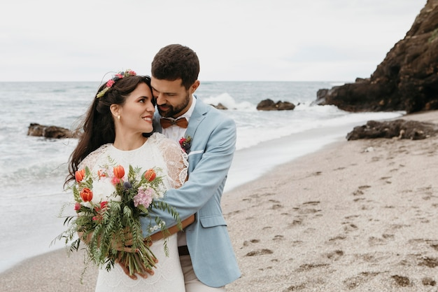 Giovane donna e uomo che hanno un matrimonio sulla spiaggia