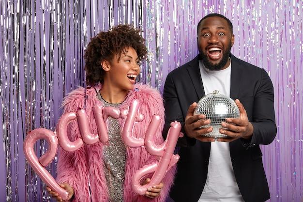 Giovane donna e uomo con palloncini festa e globo da discoteca