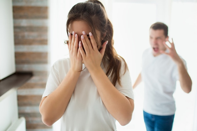 Young woman and man in room. wife stand in front and cry. covering her face with hands. husband scream and shout on woman. emotional sickness and psychological problems.