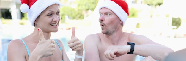 Young woman and man in santa claus hats in pool invites thumbs up gesture and smiles into laptop