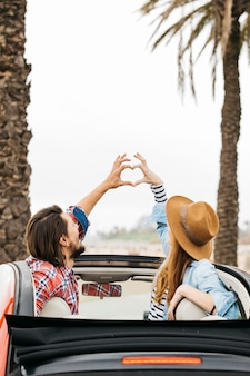 Young woman and man showing symbol of heart and leaning out from car