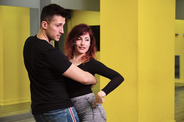 A young woman and a man teaching salsa and bachata