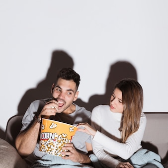 Young woman and man watching tv and eating popcorn on settee