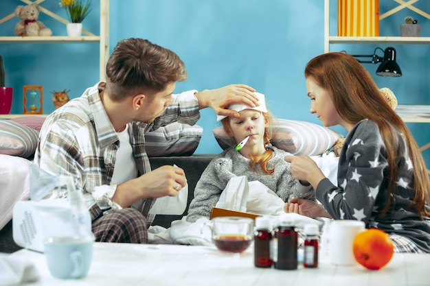 The young woman and man with sick daughter at home. home treatment. fighting with a desease. medical healthcare. family iilness. the winter, influenza, health, pain, parenthood, relationship concept