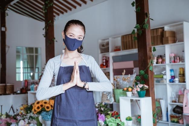 エプロンとフェイスマスクを身に着けている若い女性マネージャー花屋立ちポーズ挨拶歓迎探しカメラ