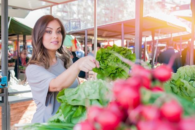 Giovane donna sul mercato. felice giovane brunetta raccogliendo alcune verdure. ritratto di bella giovane donna che sceglie verdure a foglia verde
