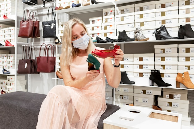 Young woman in a mask in a shoe store. shopping during the coronavirus pandemic.
