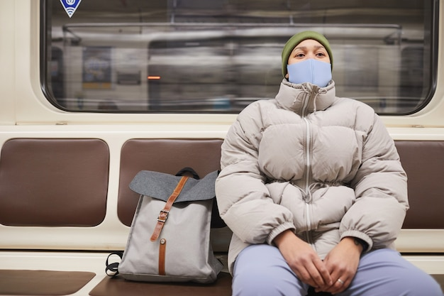 Young woman in mask and in warm clothing sitting on a train underground